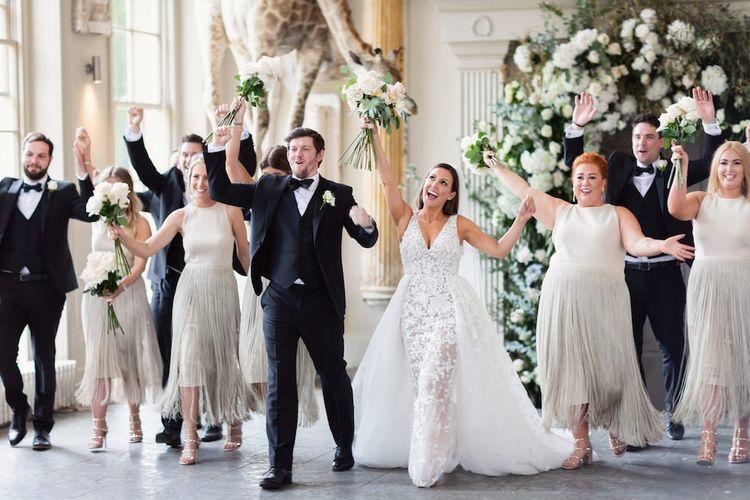 新娘和新郎与佩带边缘礼服和伴郎的伴娘在黑色领带