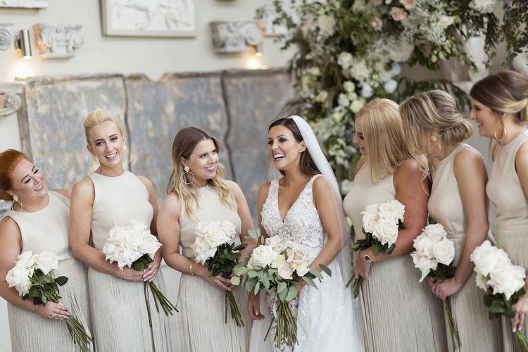 穿着Zuhair Murad连衣裙的新娘与长的面纱和白色玫瑰花束合作