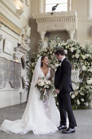新娘和新郎在与美丽的白色花卉装饰的Aynhoe公园系结
