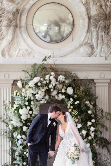 在美丽的白色花卉箍装饰前面的新娘和新郎亲吻