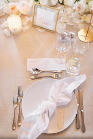 与白玫瑰和蜡烛的美丽的桌装饰