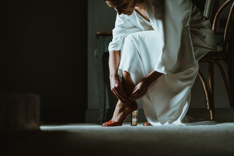 Bride wearing statement red heels tucked under elegant dress at winter wedding
