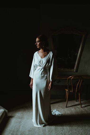 Bride wearing elegant Charlie Brear dress with long sleeve bridal top and belt