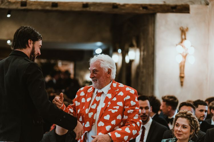Guest wearing bright red suit at winter wedding in Northumberland