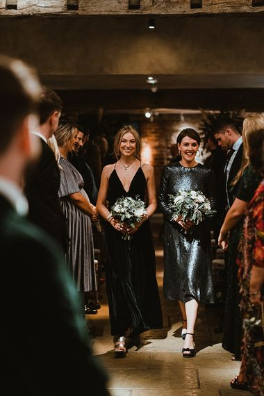 Bridesmaids wearing black dresses and white floral bouquets