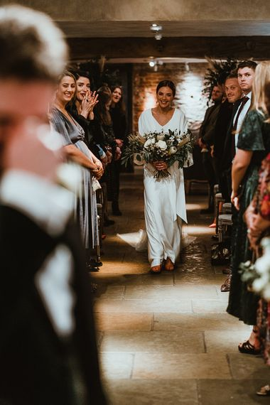 Bride wearing elegant three piece bridal dress and white floral bouquet