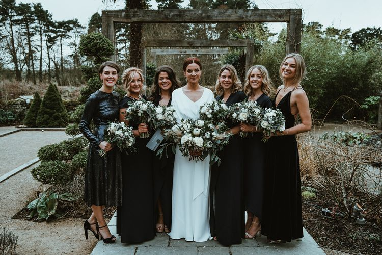 Bride and her bridesmaids wearing black dresses and white floral bouquets