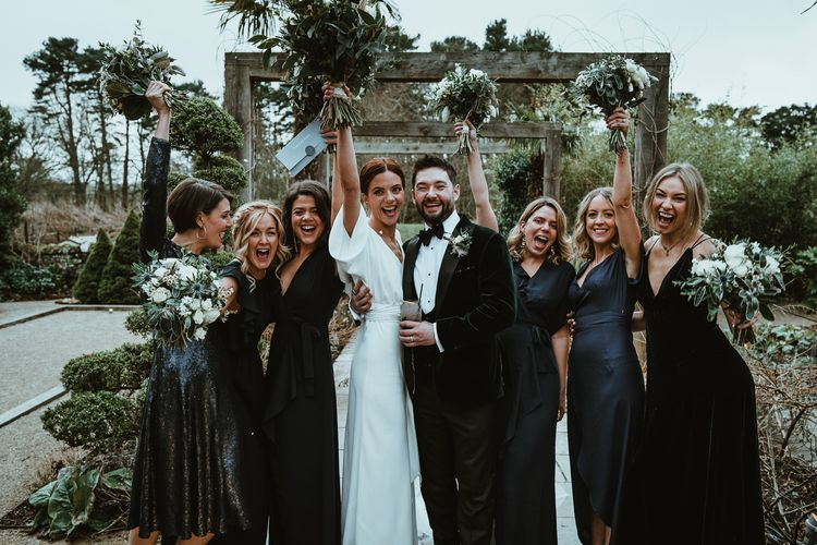 Bride and groom with  her bridesmaids wearing black dresses and white floral bouquets