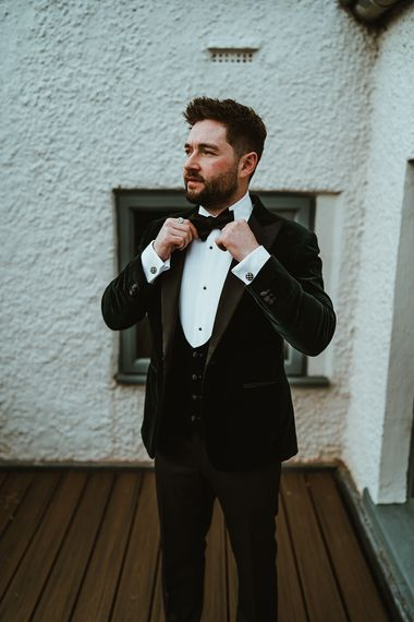 Groom wearing custom made velour three piece suit and bow tie at winter wedding
