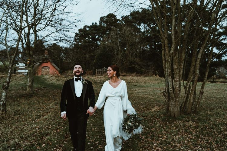 Bride wearing elegant dress and white floral bouquet with her groom wearing three piece suit and bow tie
