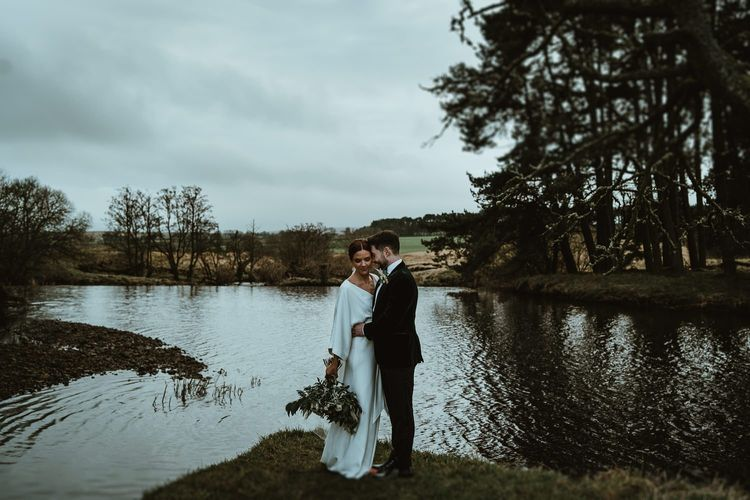 Bride and groom steal a moment at winter wedding wearing elegant Charlie Brear dress with white foliage bouquet
