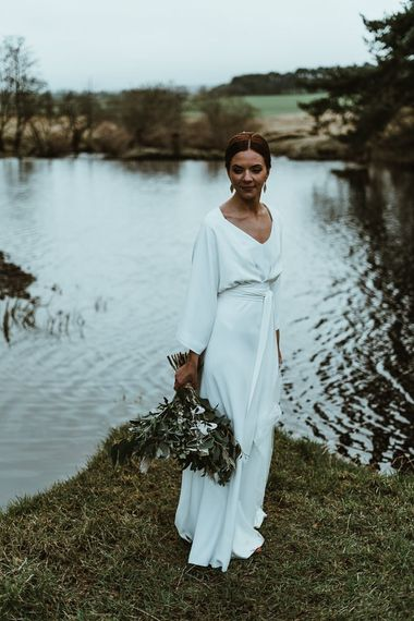 Bride wearing elegant three piece Charlie Brear dress with long sleeve top and detachable belt