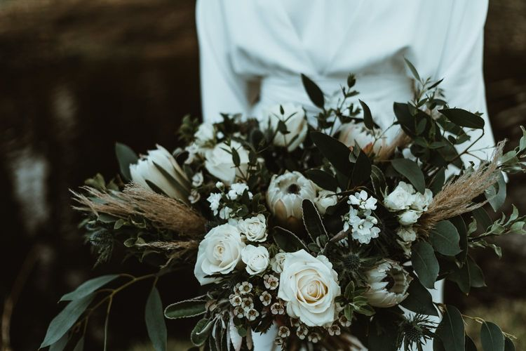 Bouquet details with white roses and foliage at winter wedding