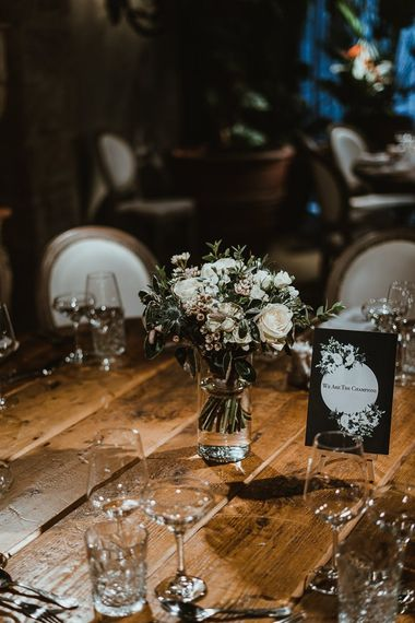 Table settings at winter wedding with white floral arrangements and black & white stationery