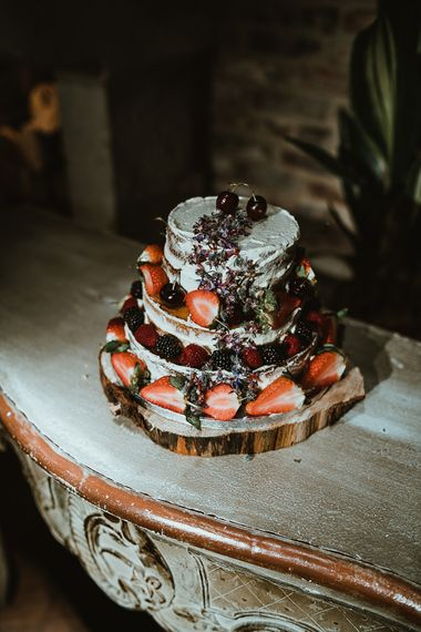 Semi-naked rustic wedding cake with fresh berries served on a tree stump