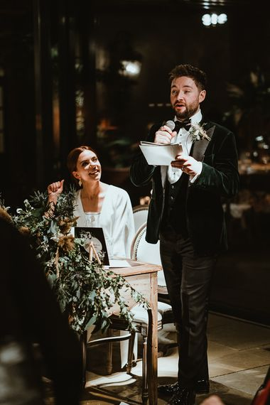 Bride and groom enjoy the speeches at winter reception with foliage styling  and winter decor