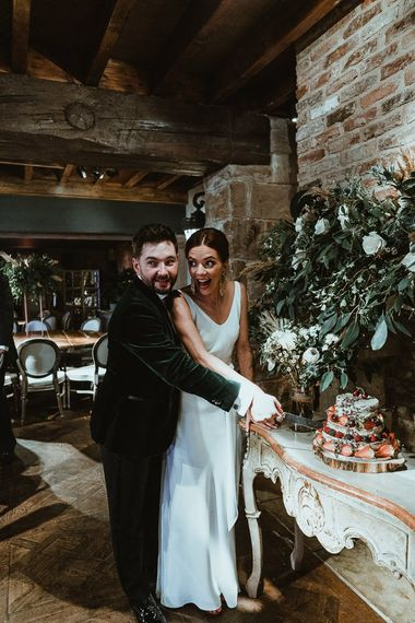 The couple cut the semi-naked cake with rustic styling and fresh berries