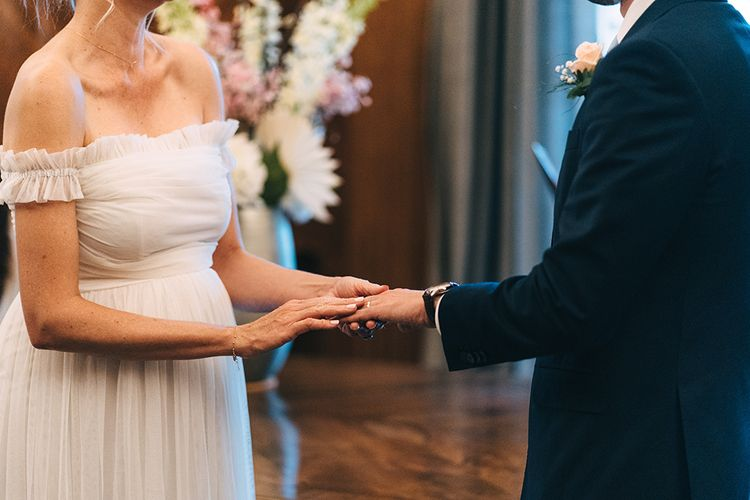 Bride and groom exchanging rings at intimate London wedding