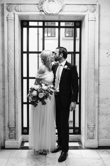 Portrait of bride in maternity wedding dress and groom in lounge suit