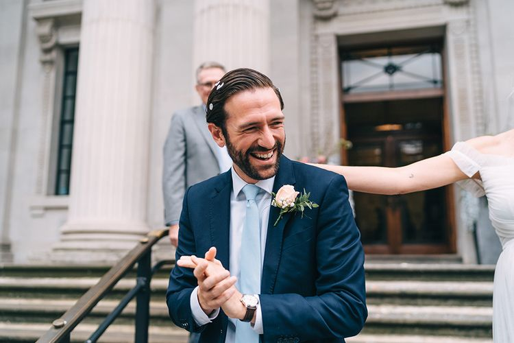 Groom in navy suit and blue tie covered in confetti