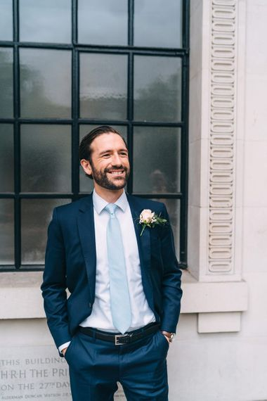 Groom in navy blue suit and baby blue tie for intimate wedding