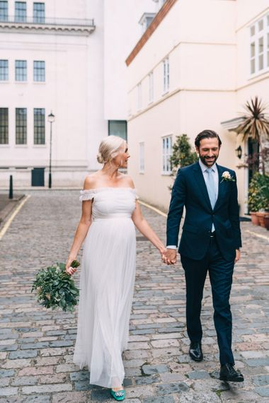 Bride and groom portrait in London with bride in maternity wedding dress
