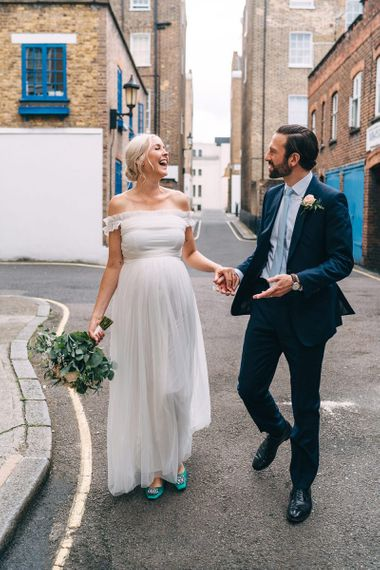Pregnant bride in maternity wedding dress and groom in navy suit in London streets