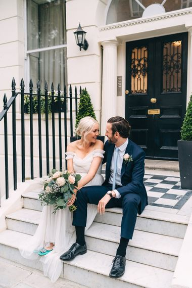 Bride and groom sitting on steps in London