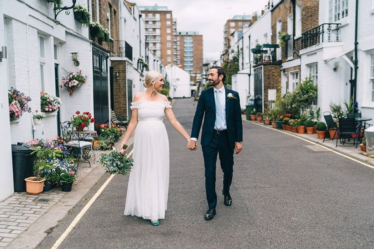 Bride and groom portrait hand in hand in London