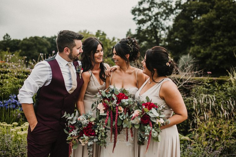 Wedding Party In Pale Grey Dresses With Red Bouquets // Glamorous Iscoyd Park Wedding With Burgundy, Navy And Ivory Colour Scheme With Artistic And Alternative Images From Carla Blain Photography