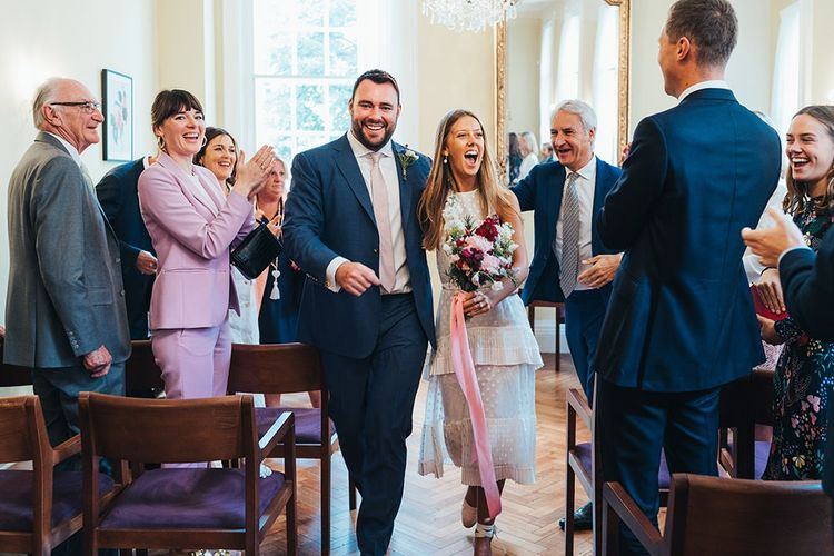 Bride and Groom Walk Back Up Aisle After Ceremony