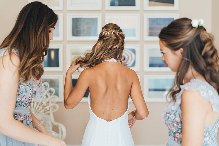 Bride Putting on Her Backless Made With Love Wedding Dress on the Wedding Morning