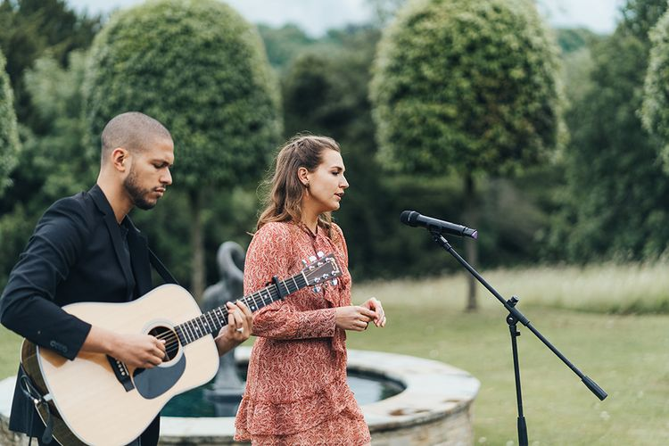 Guitarist and Vocalist Performing at the Outdoor Wedding Ceremony