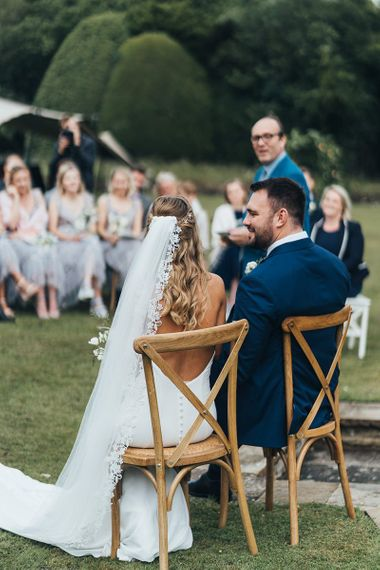 Bride in Backless Made With Love Wedding Dress and Lace Edged Veil and Groom in Navy Suit Sitting on Wooden Chairs During the Outdoor Wedding Ceremony