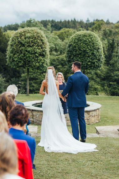 Bride in Made With Love Wedding Dress and Groom in Navy Suit Exchanging Vows at The Outdoor Wedding Ceremony