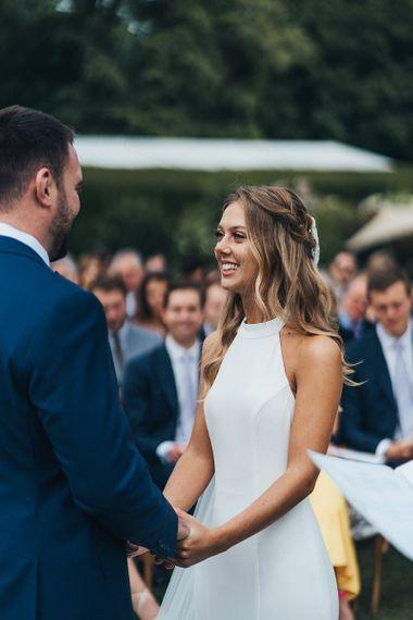 Bride in Halterneck Wedding Dress Smiling at Her Groom During The Outdoor Wedding Ceremony