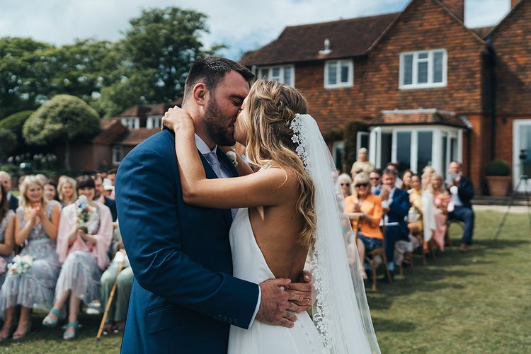 Bride in Backless Made With Love Wedding Dress and Lace Edge Cathedral Length Veil Kissing Her Groom in a Navy Suit at the Altar