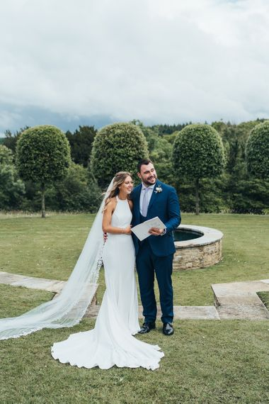 Bride in Halterneck Wedding Dress and Groom in Navy Suit Just Married