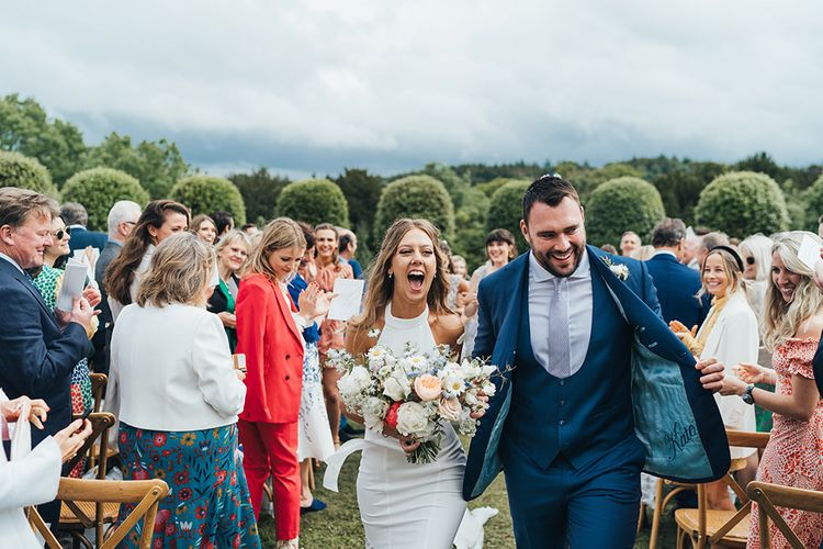 Bride in Halterneck Wedding Dress and Groom in Navy Suit Walking Up the Aisle as Husband and Wife