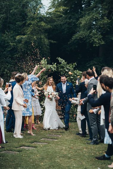 Confetti Moment with Bride in Halterneck Wedding Dress and Groom in Navy Suit with Horseshoe Waistcoat