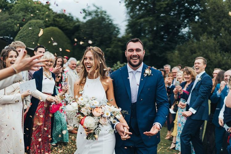 Confetti Moment with Bride in Made With Love Wedding Dress Holding a Spring Bouquet and Groom in Three-Piece Navy Suit