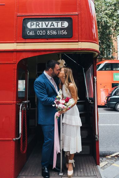 Bride and Groom Kiss On Red Bus Wedding Transport