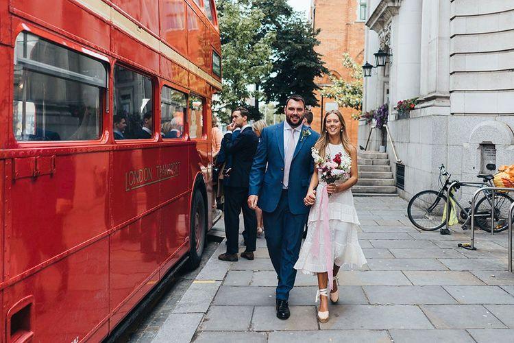 Happy Couple Walk Next To Bus Wedding Transport