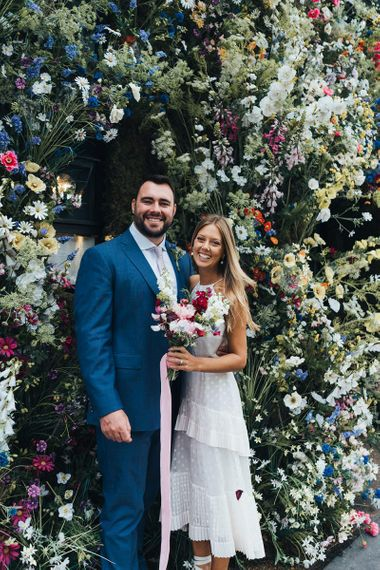 Bride and Groom Smile With Flowers