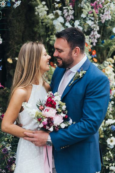 Bride and Groom In Navy Suit With Pink Flowers