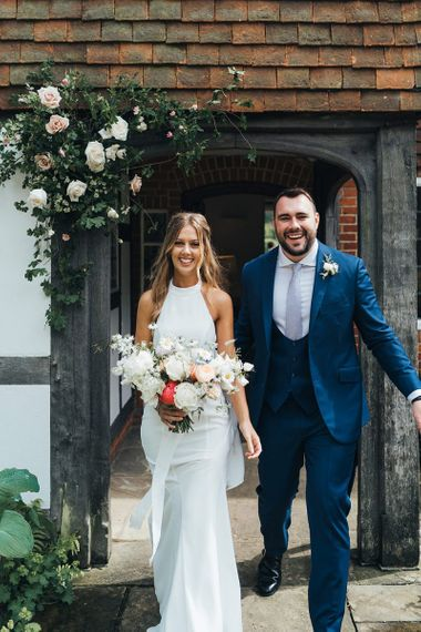 Bride in Halterneck Made With Love Wedding Dress and Groom in Navy suit with Horseshoe Waistcoat
