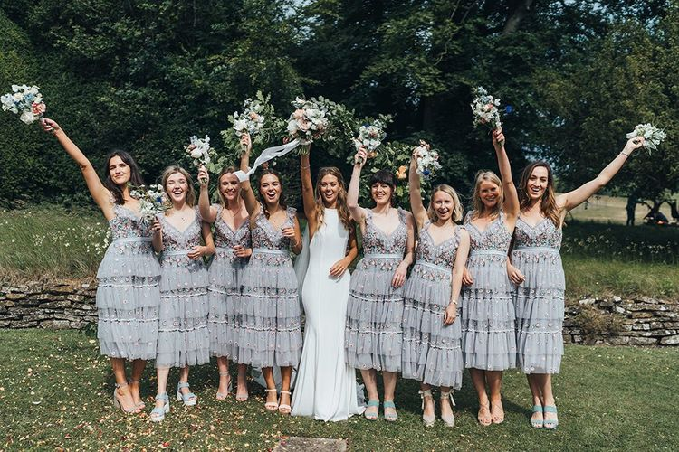 Bridal Party Portrait with Bridesmaids in Needle and Thread Dresses and Bride in Made With Love Wedding Dress Waving Their Bouquets in the Air