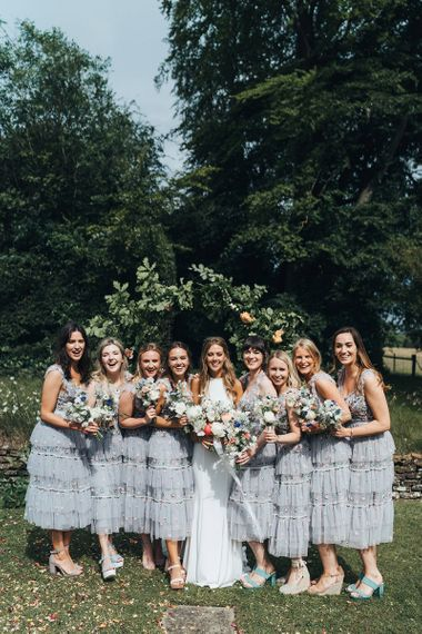 Bridal Party Portrait with Bridesmaids in Needle and Thread Dresses and Bride in Made With Love Wedding Dress Holding Bright Bouquets