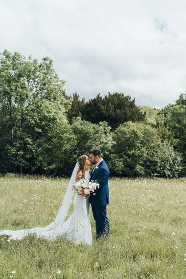 Bride in Halterneck Made With Love Wedding Dress and Groom in Navy Suit Kissing In a Field