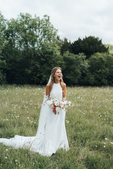 Bride in Halterneck Made With Love Wedding Dress Holding a Romantic Wedding Bouquet in a Field